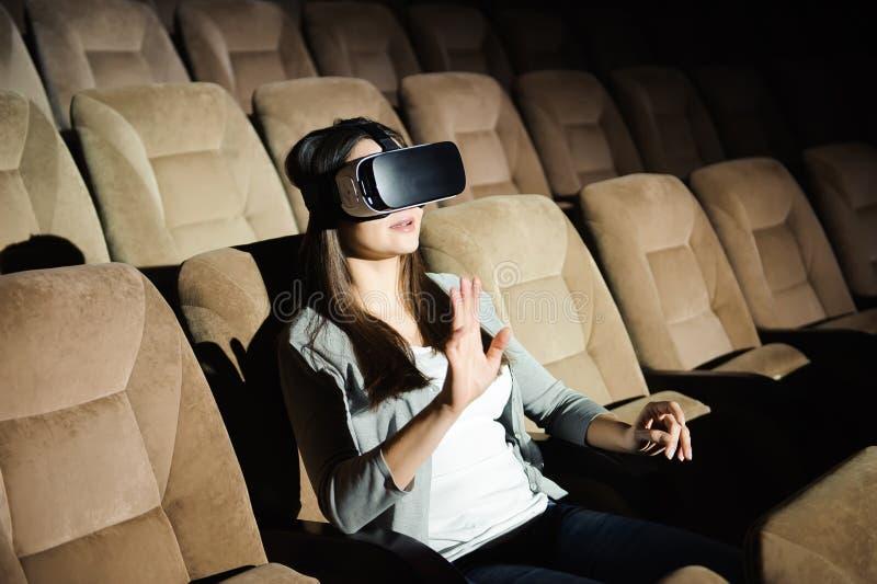 Ung flicka med virtuell verklighetexponeringsglas i en mjuk stol royaltyfria foton
