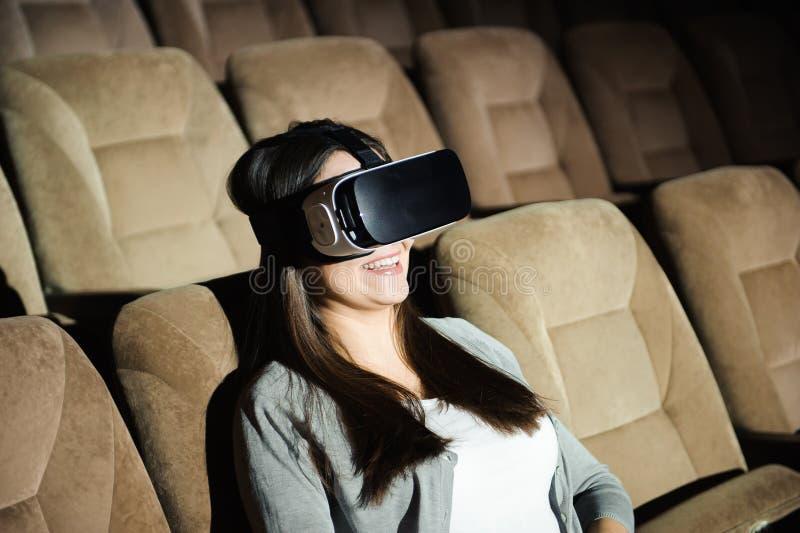 Ung flicka med virtuell verklighetexponeringsglas i en mjuk stol arkivbild
