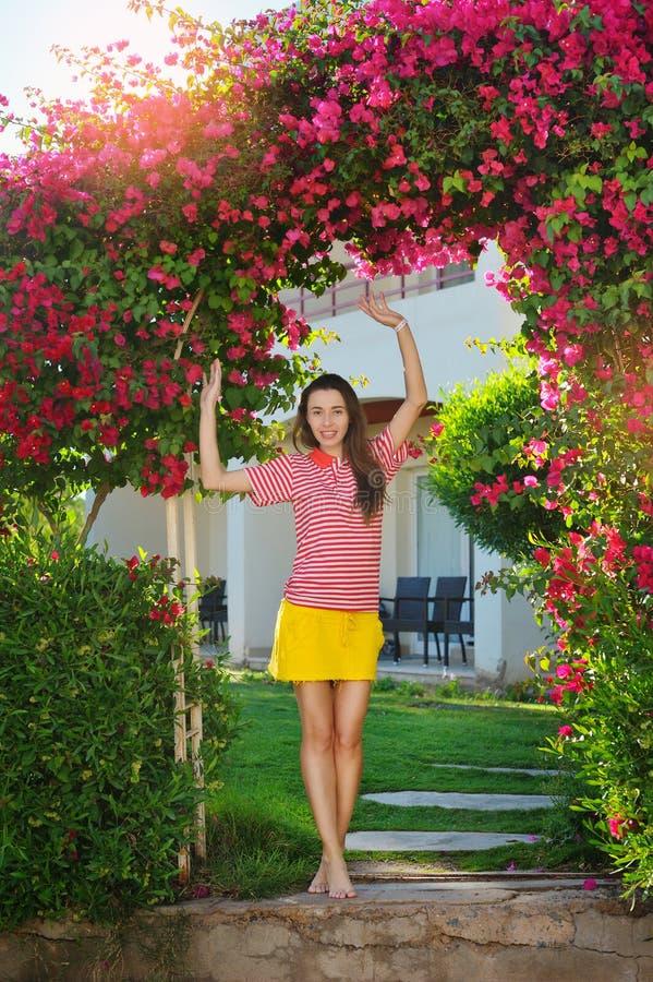 Ung flicka nära bågen med röda blommor arkivfoton
