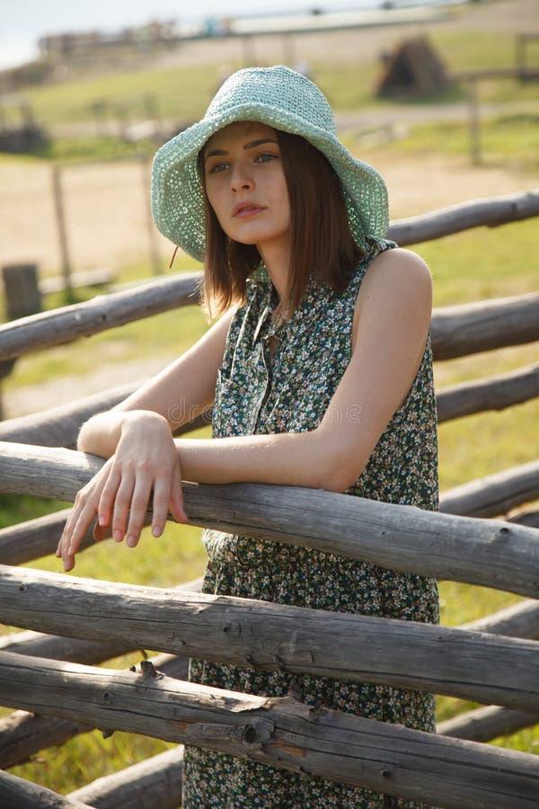 Ung flicka nära det wood staketet arkivbild