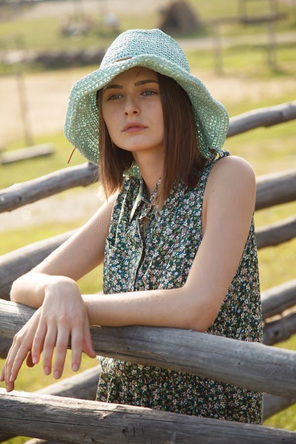 Ung flicka nära det wood staketet arkivfoton