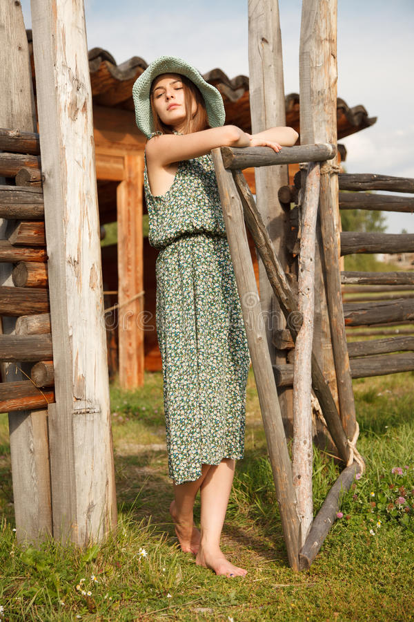 Ung flicka nära det wood staketet arkivfoto
