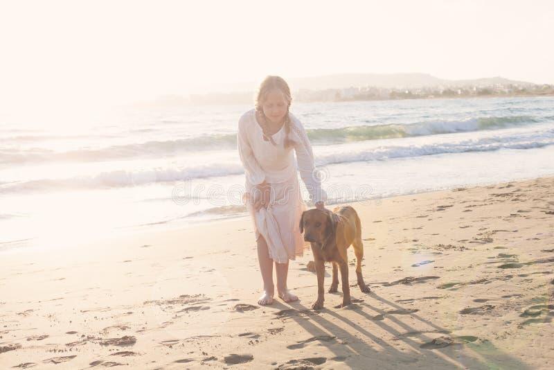 Ung flicka och hund som promenerar kusten royaltyfri bild