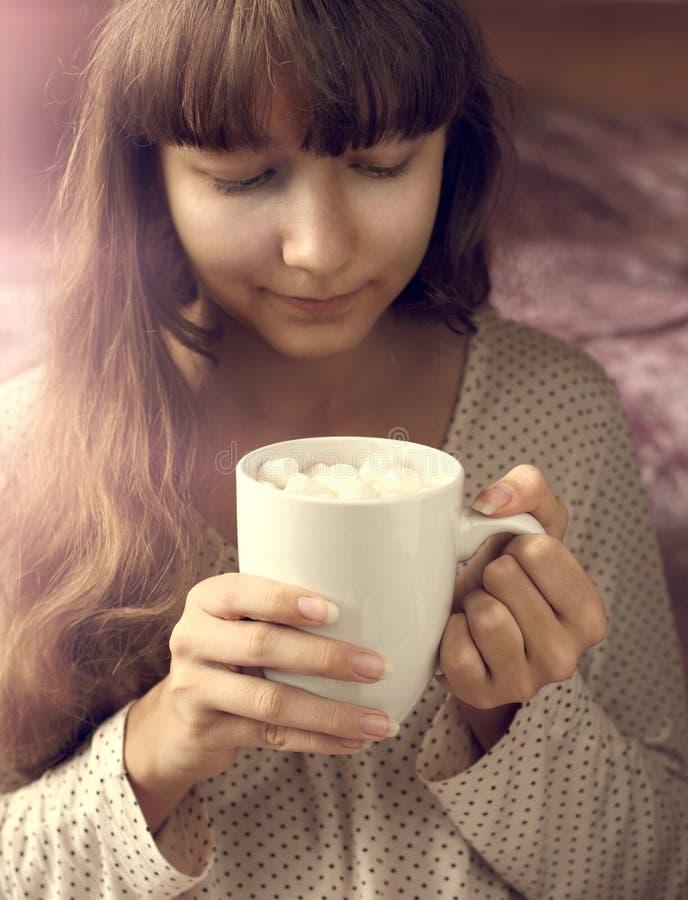 Ung flicka och kopp av varm choklad med marshmallower i morgonen royaltyfri bild