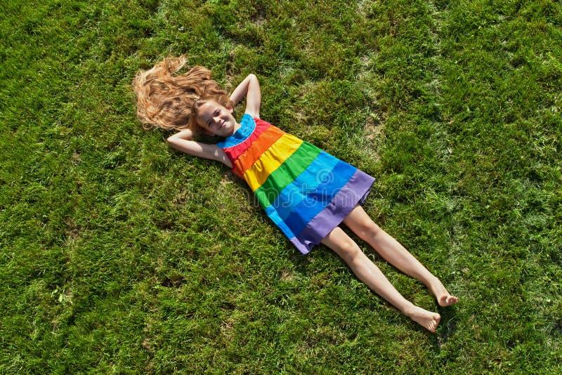 Ung flicka på att ligga på nytt mejad gräsmatta royaltyfri foto