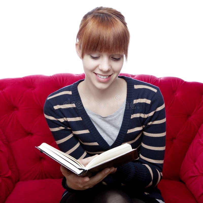 Ung flicka på den röda sofaen läste en bok royaltyfri bild