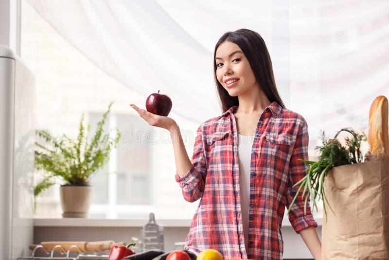 Ung flicka på den sunda livsstilen för kök som lutar på tabellen nära påse med produkter som ser det nyfikna visande äpplet för k arkivbild