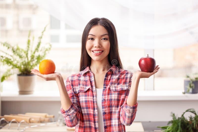 Ung flicka på det sunda livsstilanseendet för kök som rymmer äpplet och apelsinen som ser glat jämföra för kamera royaltyfri foto