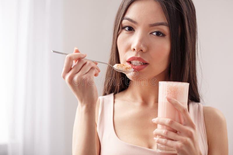 Ung flicka på det sunda livsstilanseendet för kök som rymmer exponeringsglas som äter smoothien som ser kameranärbild fotografering för bildbyråer