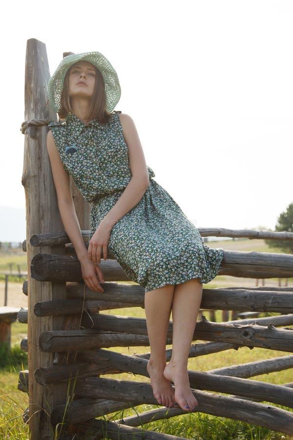 Ung flicka på det wood staketet arkivfoton