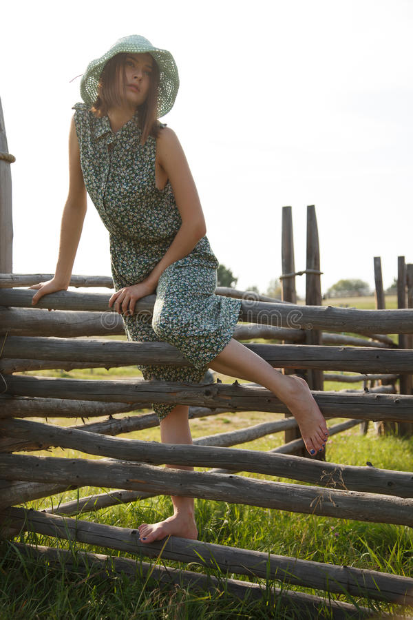Ung flicka på det wood staketet royaltyfri foto