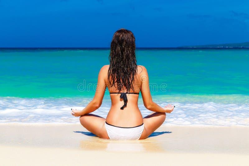 Ung flicka på en tropisk strand Resa resväskan med seascapeinsida royaltyfria foton