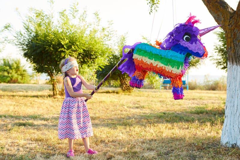 Ung flicka på ett utomhus- parti som slår en pinata royaltyfri bild
