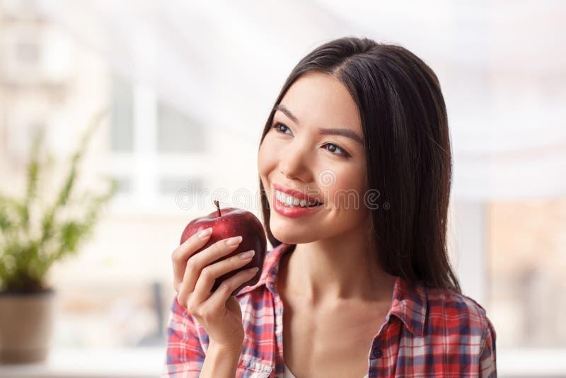 Ung flicka på för livsstilanseende för kök som det sunda äpplet för innehav ut ser den glade närbilden för fönster royaltyfri foto