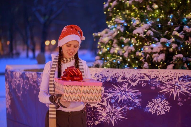 Ung flicka på julafton under julgranen arkivfoto