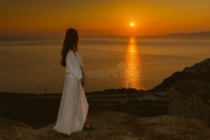 Ung flicka på kanten av en klippa i en vit klänning som håller ögonen på solnedgången i Santorini, Grekland Kvinnlig i vita sundr arkivfoton