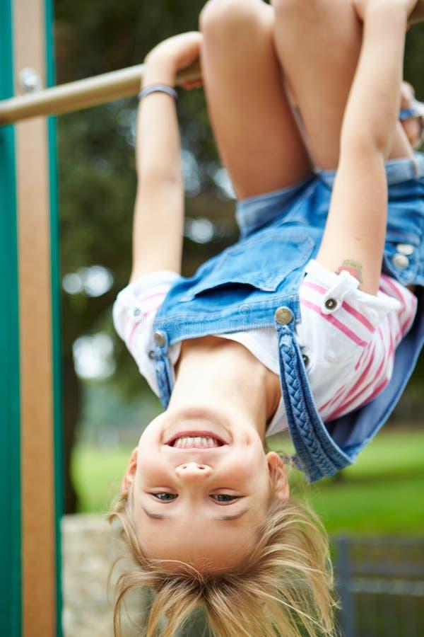 Ung flicka på klättringram i lekplats royaltyfri bild