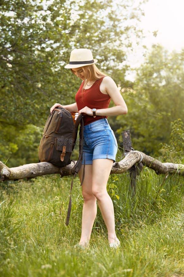 Ung flicka på naturen med hatten och ryggsäcken Sommar royaltyfri bild