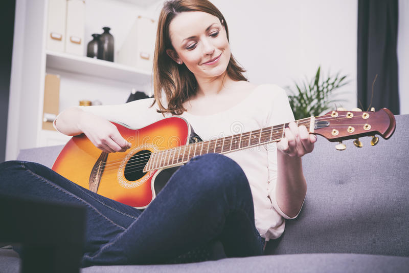 Ung flicka på soffan som spelar gitarren arkivfoto