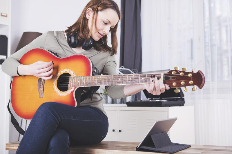 Ung flicka på soffan som spelar gitarren royaltyfri bild