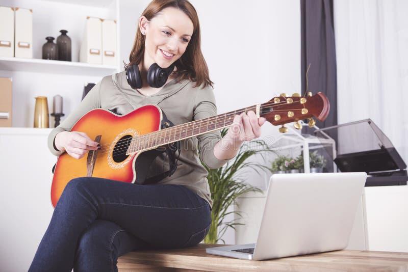 Ung flicka på soffan som spelar gitarren royaltyfria bilder