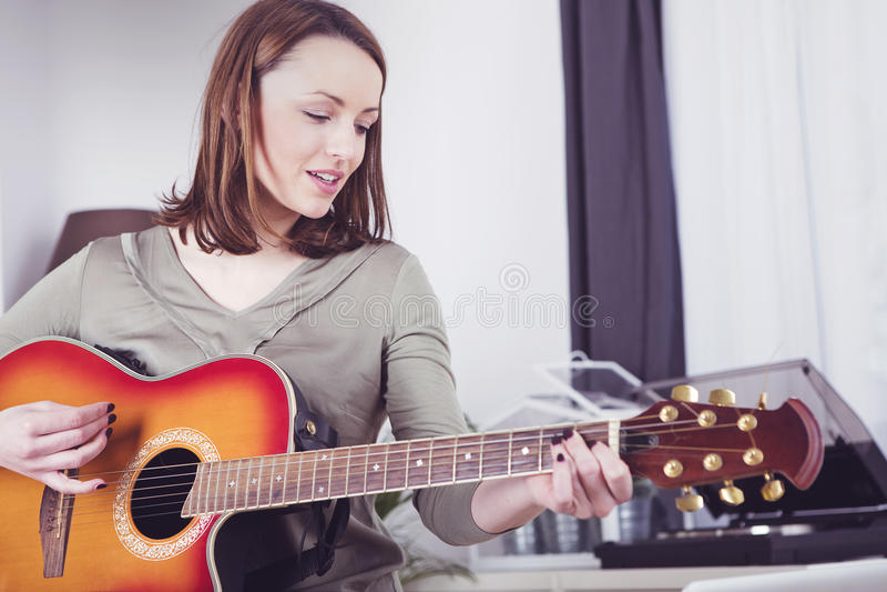 Ung flicka på soffan som spelar gitarren arkivfoton