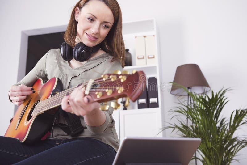 Ung flicka på soffan som spelar gitarren arkivbild