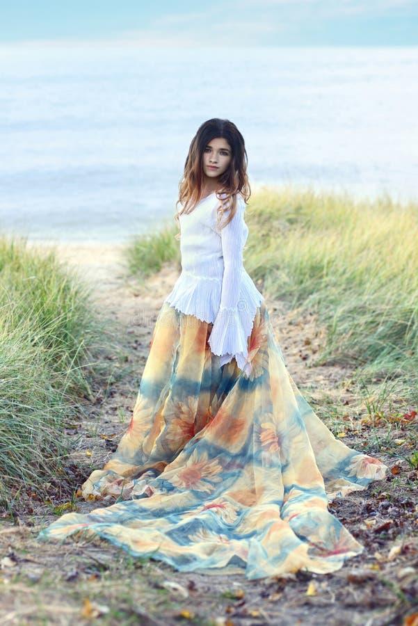 Ung flicka på stranden med blommaklänningen arkivfoto