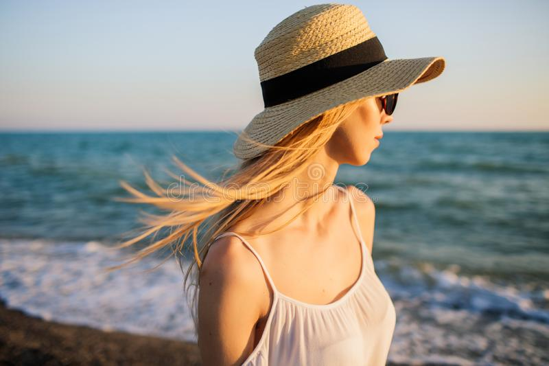 Ung flicka på stranden som ser vågor arkivbild