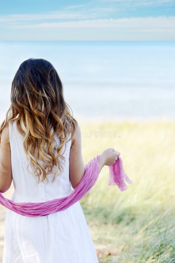 Ung flicka på strandrosa färghalsduken arkivbilder