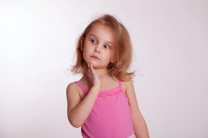 Ung flicka på vit som ser upp och till hennes rätt fotografering för bildbyråer