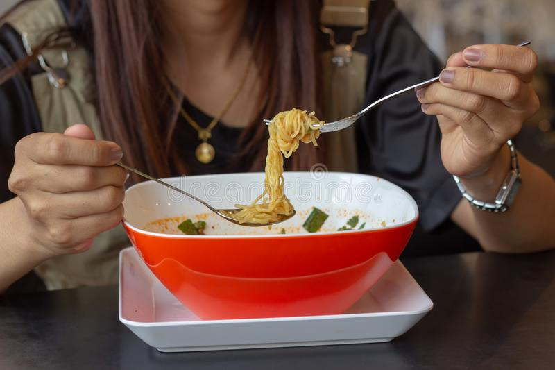 Ung flicka som äter nudlar, i all hast lunch, Tom Yum Noodles arkivbilder