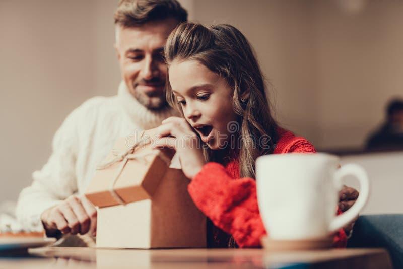 Ung flicka som öppnar den bruna närvarande asken i kafé royaltyfria foton
