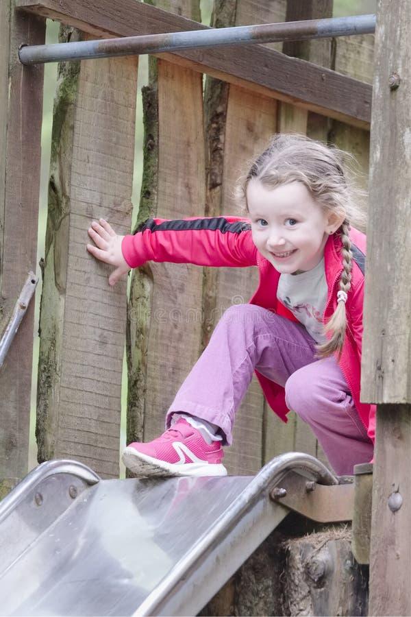 Ung flicka som överst skrattar och ler av glidbana på den utomhus- affärsföretaglekplatsen royaltyfri bild