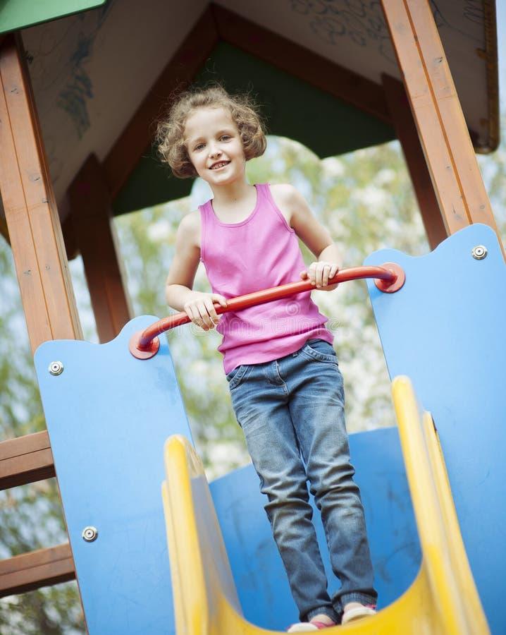 Ung flicka som överst står av glidbana i lekplats royaltyfri bild