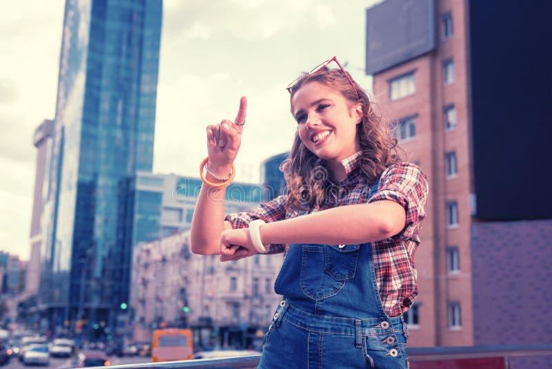 Ung flicka som använder gester, medan spela den roliga leken med hennes vänner utanför arkivfoto