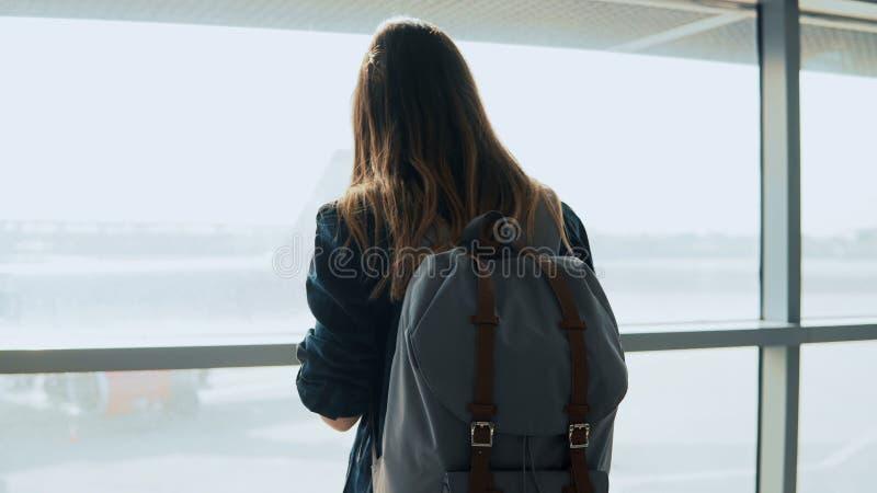 Ung flicka som använder smartphonen nära flygplatsfönster Den lyckliga europeiska kvinnan med ryggsäcken använder mobilen app i t royaltyfri fotografi