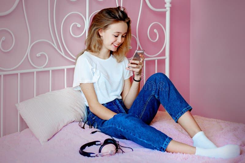 Ung flicka som använder smartphonen som sitter på sängen arkivbild