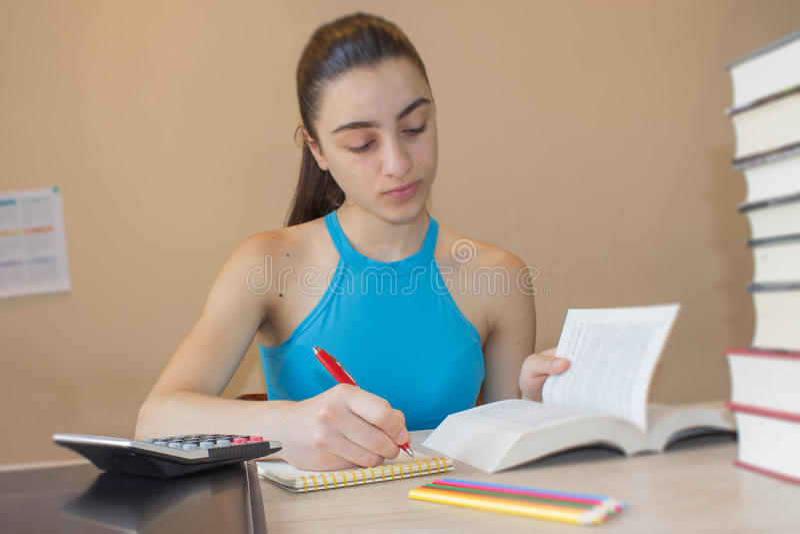 Ung flicka som arbetar på hans läxa Stående av den nätta flickahögstadiumstudenten som studerar och skriver fotografering för bildbyråer