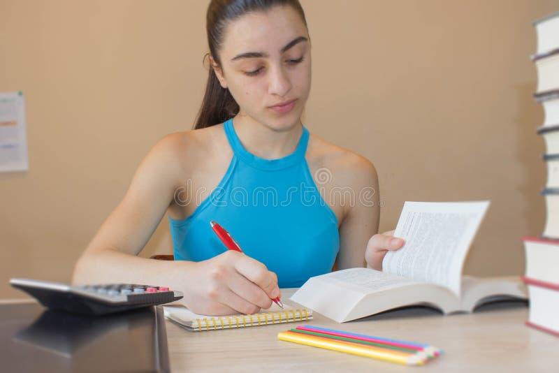 Ung flicka som arbetar på hans läxa Stående av den nätta flickahögstadiumstudenten som studerar och skriver arkivbilder