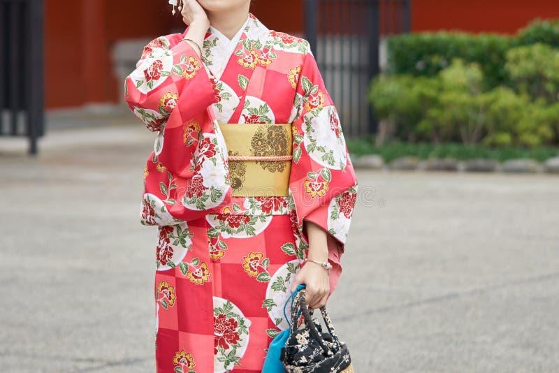 Ung flicka som bär den japanska kimonot som framme står av den Sensoji templet i Tokyo, Japan Kimonot är ett japanskt traditionel royaltyfria bilder