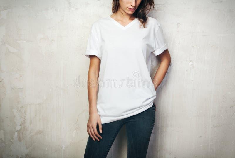 Ung flicka som bär den tomma t-skjortan och svart jeans konkret ljus medelfläckvägg för bakgrund royaltyfri fotografi