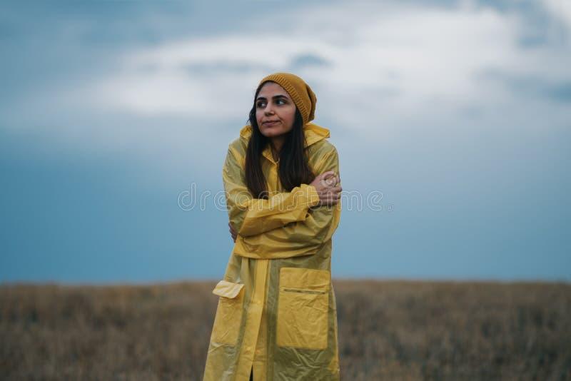 Ung flicka som bär en gul regnrock i regnig och kall dag royaltyfri bild