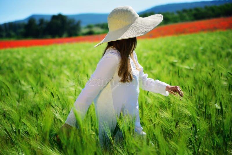 Ung flicka som bär en hatt i en vit klänning i ett grönt vetefält royaltyfria foton