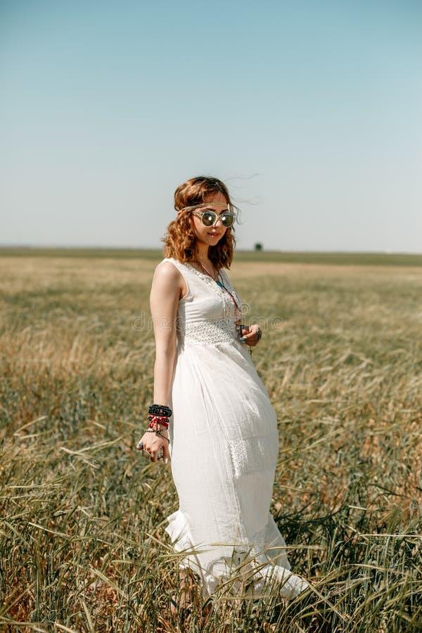 Ung flicka som bär en vit klänning i hippiestil som poserar i ett vetefält royaltyfria bilder