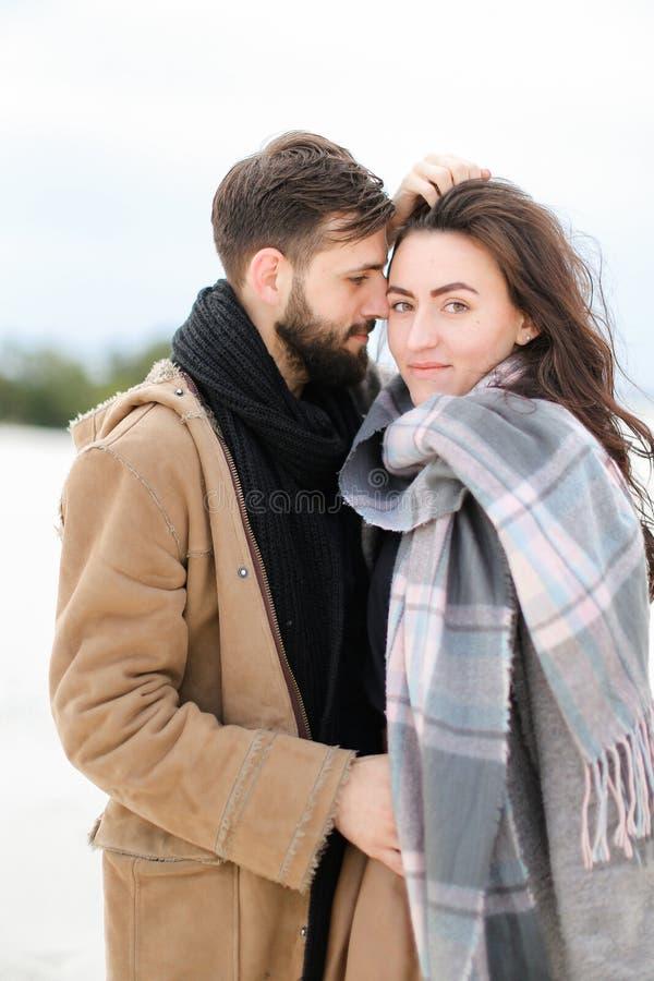Ung flicka som bär grått halsdukanseende med mannen i laget, vintervitbakgrund arkivbilder