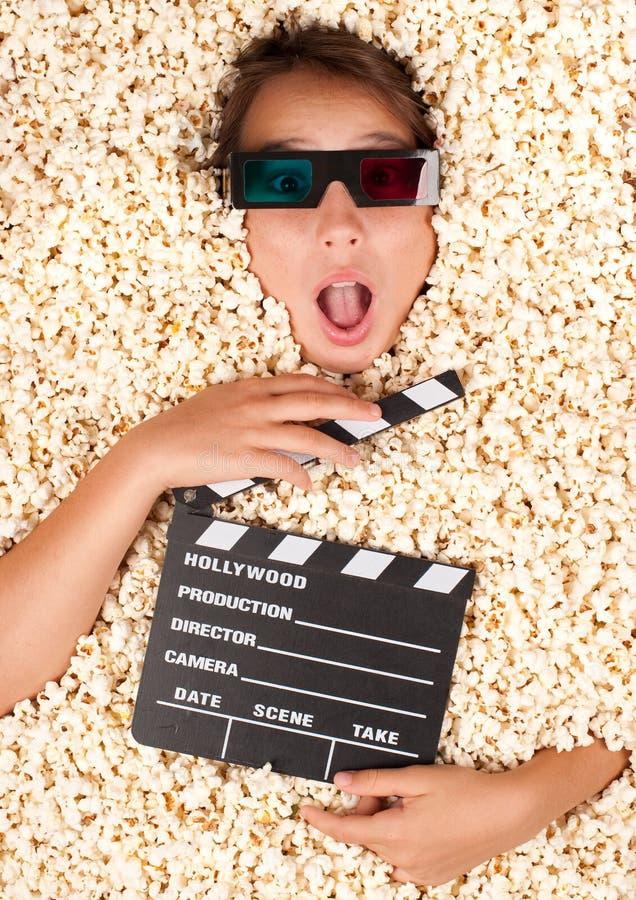 Ung flicka som begravas i popcorn royaltyfri bild