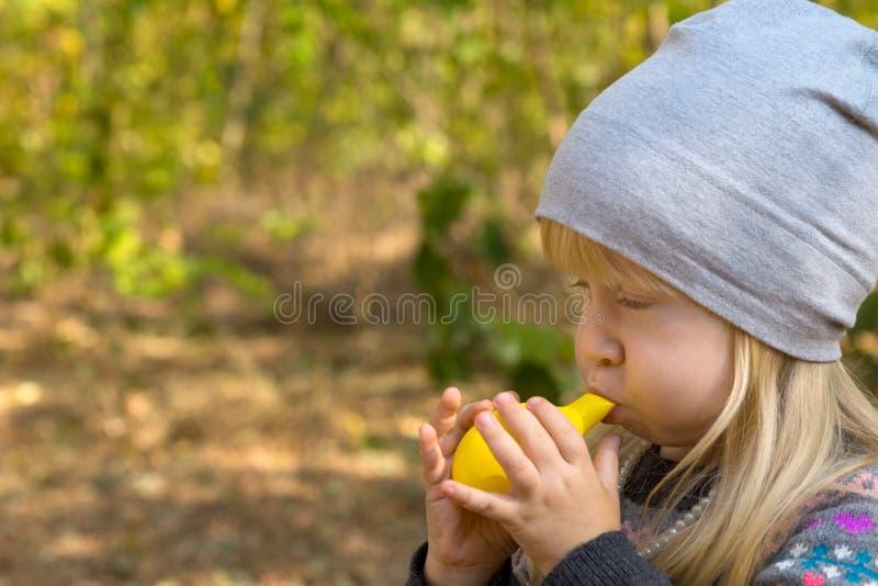 Ung flicka som blåser den gula ballongleksaken royaltyfria foton