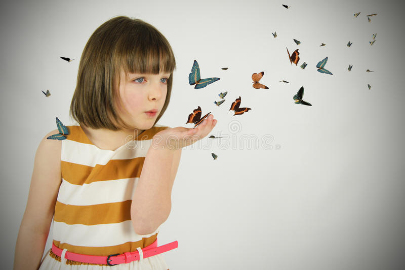 Ung flicka som blåser fjärilar royaltyfri fotografi