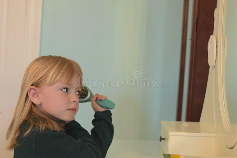Ung flicka som borstar hår på fåfänga royaltyfri fotografi